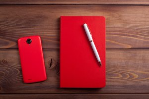 Red notebook and a smartphone on  dark wooden background.