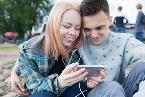 Young couple watching a video on a smartphone on the beach of the river. They smile, seeing the funny video