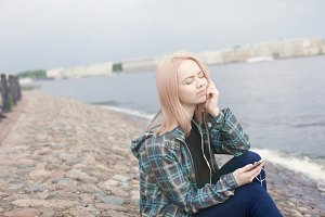 Young beautiful girl sitting on the beach and listening to music on your smartphone. She is resting and thinking