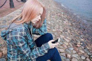 Young beautiful girl sitting on the beach and listening to music on your smartphone