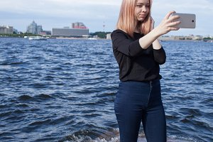 Young cute girl makes selfie on the waterfront of St. Petersburg