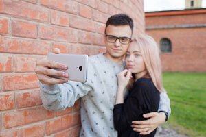 Young couple photographing a selfie with smartphone on the background of red brick wall. Blonde girl with blue eyes and a young man of Arab appearance with brown eyes