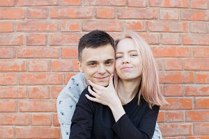 Happy young couple hugging and smiling on a background of red brick wall. Blonde girl with blue eyes and a young man of Arab appearance with brown eyes