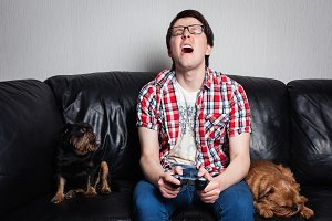 A young man in a red shirt and blue jeans sits at home and plays video games together with their dogs. Poor guy is crying and angry because of fail. the concept of emotions