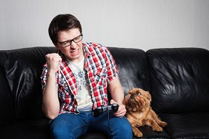 Young man playing game at home. Attractive man is wearing eyeglasses. He is happy to win this fight. Boy lifting his fist above. Sitting next to red dog and looking for a master