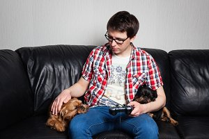 A young man in a red shirt and blue jeans sits at home and plays video games together with their dog. The guy took a break to pet their Pets. the concept of love and care