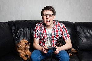 A young man in a red shirt and blue jeans sits at home and plays video games together with their dog. Screaming boy in front of tv trying to fight with his enemies. Dog looking at his master