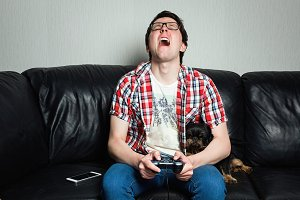 A young man in a red shirt and blue jeans sits at home and plays video games together with their dog. Poor guy is crying and angry because of fail. the concept of emotions