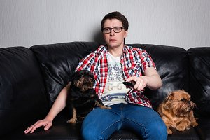 A young man in a red shirt and blue jeans watching TV with two dogs sitting on a black leather sofa. Changing the channels on the remote