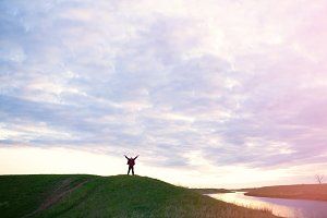 happy man with raised hands by the river on a sunset sky background