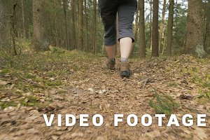 Legs of the young girl with backpack in the summer forest - flying camera shot