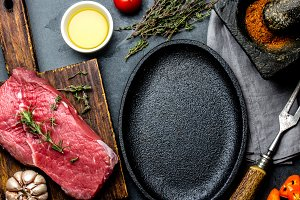 Raw fresh meat steak beef tenderloin, herbs and spices around frying pan plate. Food cooking ackground with copy space