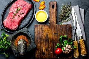 Fresh raw meat steak beef tenderloin, herbs and spices around cutting board. Food cooking background with copy space