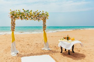 Wedding arch decorated with flowers on a tropical sand beach. Outdoor beach wedding setup