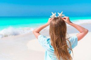 Back view of little girl having fun on white sandy beach
