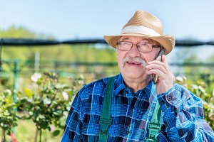 Senior gardener talking on the phone with a client.
