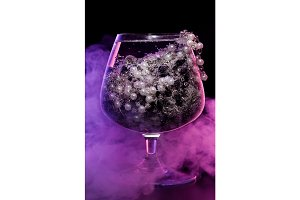 Glass with jewelry in smoke