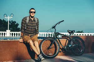 Young Man Cyclist Sitting With Sunglasses And Baclpack Near Fountain Next To Bicycle In Summer Park Daily Lifestyle Urban Resting Concept