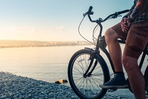 Unidentifiable young man cyclist rests while sitting on a bicycle on the seashore and enjoys the view of the sea and the dawn