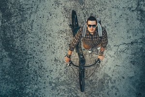 Young Man Cyclist In Glasses With Backpack Riding On Bike Down The Street, Top View. Daily Lifestyle Urban Resting Concept