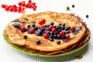 Thin pancakes stack with fresh summer berries