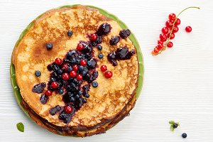 Thin pancakes with summer berries on white wooden table