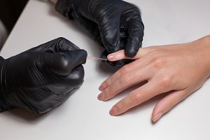 Manicurist black gloves doing a manicure at the beauty salon on a white background. Nail Polish colors Nude. Beautiful women's hands