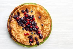 Thin pancakes with fresh summer berries on white wooden table