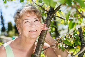 Attractive mature woman embracing nature. Grandmother