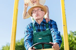 Grandfather taking grandmother for ride on tractor trailer across countryside