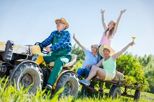 Senior man taking family for ride on tractor