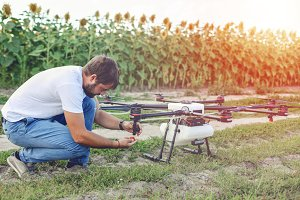 Young engineer preparing surveillance drone in field.