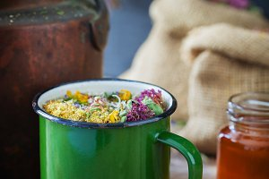 Mug of healing herbs, old tea kettle