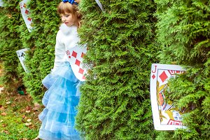 An little beautiful girl standing near the fir trees and looking down at the playing cards