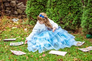 An little beautiful girl in a long blue dress sitting on the grass and playing with large game cards