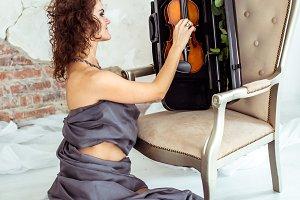 Beautiful woman touching violin