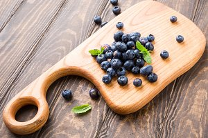 Freshly picked blueberries on wooden board