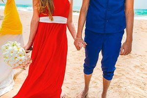 A picture of a happy couple holding hands at the beach. Newlyweds at the honeymoon. Close-up