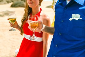 Young happy couple drinking white wine on the beach, closeup