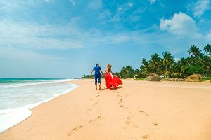 Honeymoon at the sea. Back view of loving couple walking away with footprints at sandy beach. Holding hands