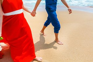 A couple walking together on the beach and holding hands. Close-up