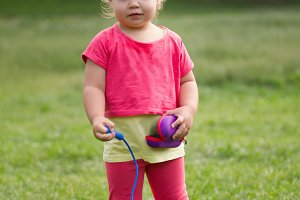 Cute Little toddler girl in pink dress playing in park in front of green grass