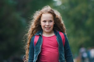 Pretty smiling child girl walking in park