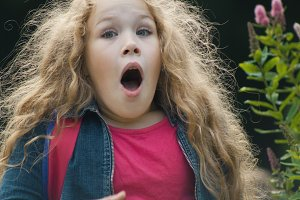 little girl with curly hair surprised - blonde child in park