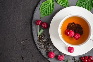 cup of tea and ripe raspberry, cherry, currant on a black background