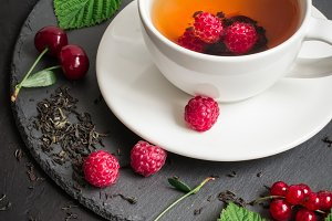 cup of Berry tea and ripe raspberry, cherry, currant on a black background