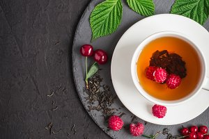 Freshly brewed tea and ripe berries on a black background