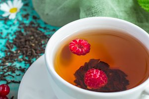 White cup of tea with raspberries closeup  on a turquoise background