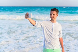 Young man taking selfie on the beach background the sea