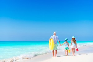 Family on white tropical beach on caribbean island. Father and little daughters on the seashore